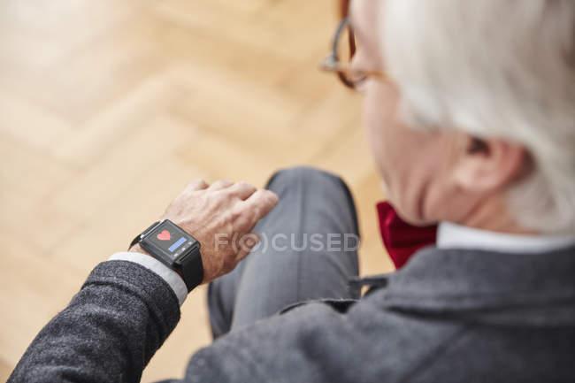 Senior man checking medical data on smartwatch — Stock Photo