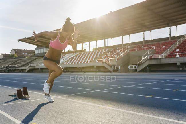 Latin sprinter woman starting race on stadium — Stock Photo