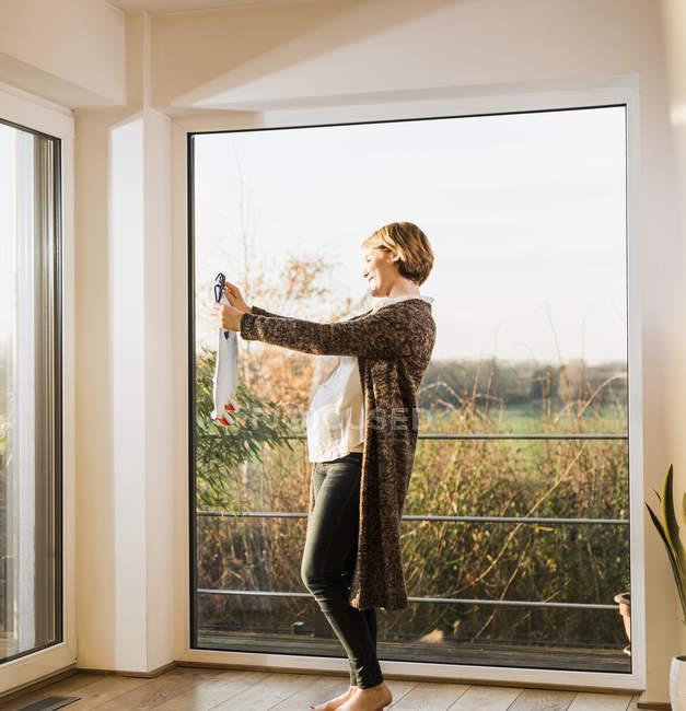 Беременная женщина стоит у окна, держа детскую одежду. — стоковое фото