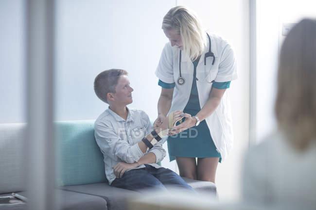 Молодая женщина-врач проверяет пациента с шиной на руке — стоковое фото