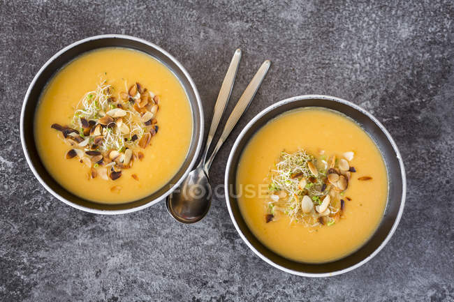 Bowls of sweet potato coconut soup with ginger, parsnip, leek, sprouts and almond — Stock Photo
