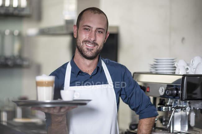 Portrait of smiling barista serving Latte Macchiato — Stock Photo
