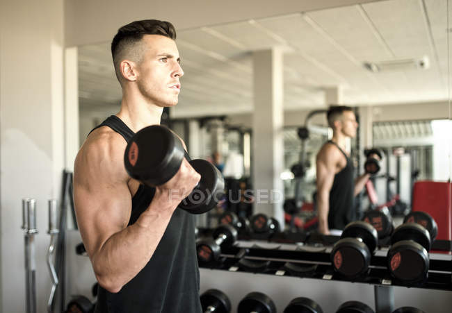 Side view of man training biceps in gym — Stock Photo