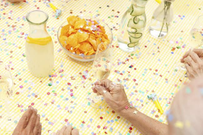 Святкування старший сидячи за столом з наполягають води, шампанське і картопляними чіпсами — стокове фото