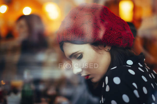 Portrait of young woman wearing red hat behind windowpane of a pub in the evening — Stock Photo