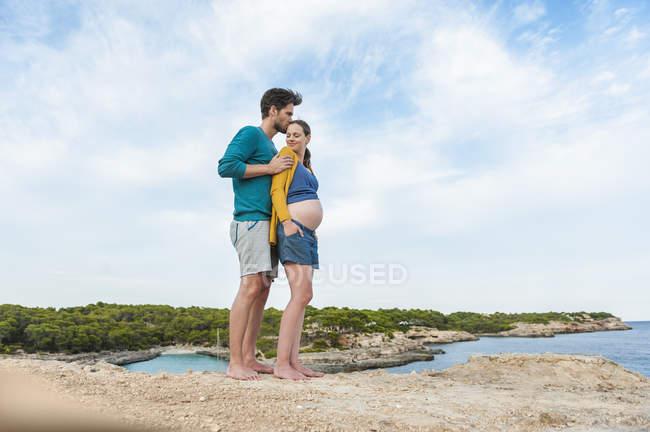 Майбутніх батьків, стоячи на морі і обіймати — стокове фото