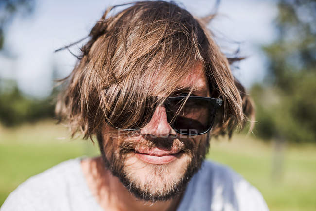 Portrait of a man with unkempt hair wearing sunglasses — Stock Photo