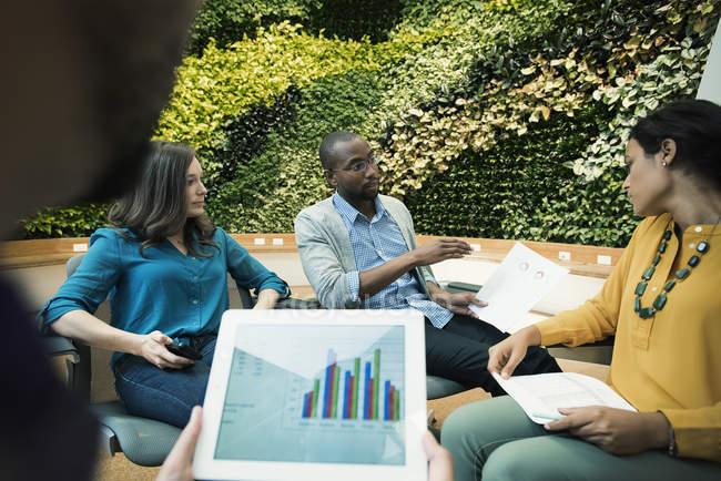 Молодые бизнесмены обсуждают перед зеленой стеной завода — стоковое фото
