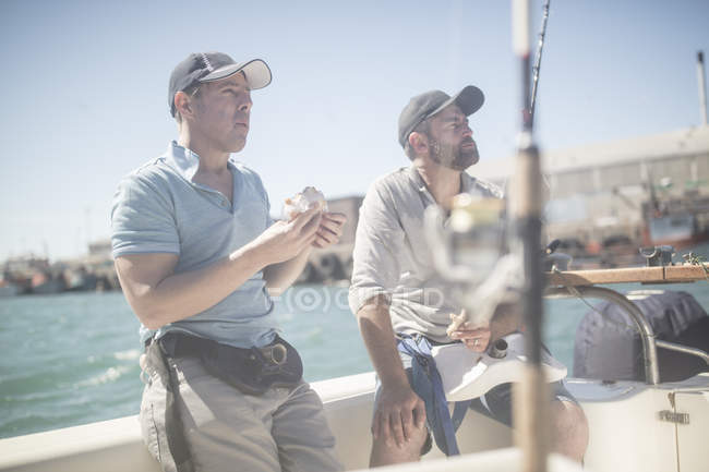 Two men having lunch break on boat with fishing rods — Stock Photo