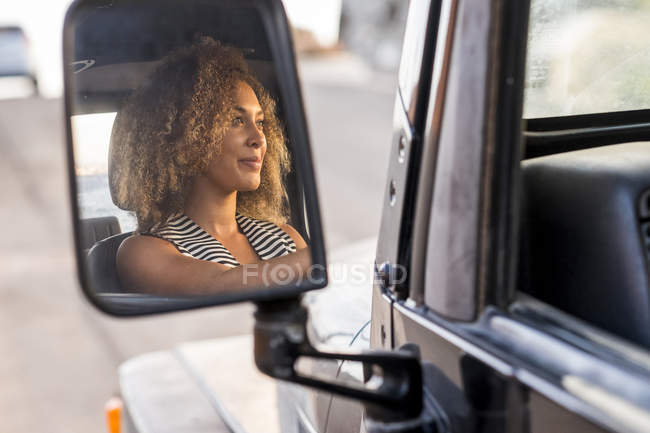 Mirror image of smiling young car driver — Stock Photo