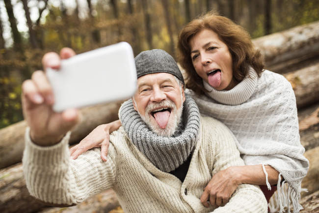 Portrait of senior couple sticking out tongues while taking selfie — Stock Photo