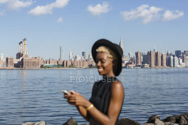 Estados Unidos, Nueva York, Brooklyn, sonriente joven y elegante mujer con teléfono inteligente en East River con el horizonte de Manhattan en el fondo - foto de stock