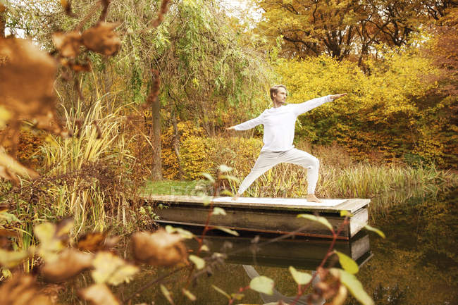 Man practicing yoga on a jetty at a pond in autumn — Stock Photo