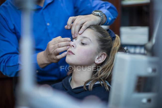 Optometrist inserting contact lens into girl's eye — Stock Photo