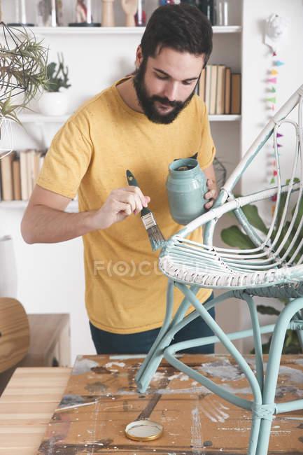 Bärtiger Mann bemalt Korbsessel zu Hause — Stockfoto