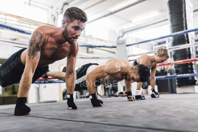 Caucasian athletes exercising in boxing club — Stock Photo