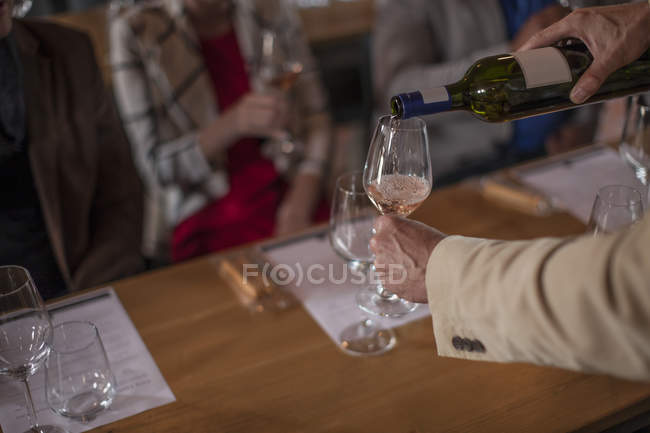 Cropped image of bartender pouring wine into glasses during wine degustation — Stock Photo