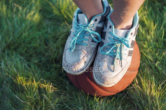 Pessoa em tênis de pé em uma bola de basquete em um prado — Fotografia de Stock