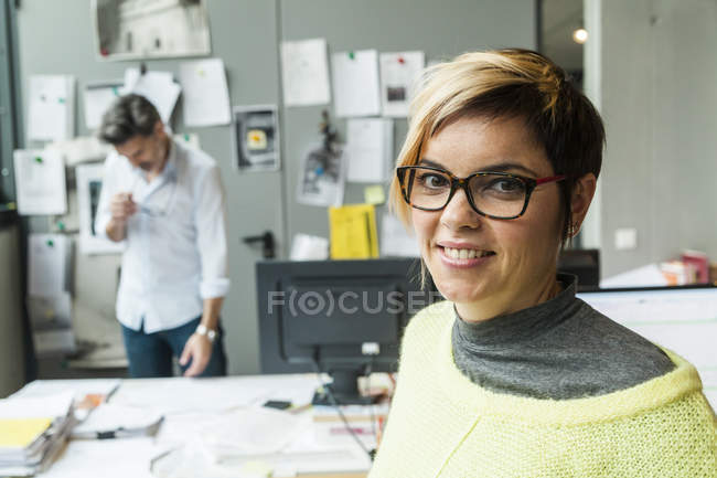 Portrait of smiling female architect standing in office with colleague on background — Stock Photo