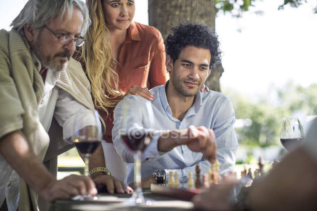 Cape Town, South Africa, Male seated with family playing chess game,wine drinks — Stock Photo
