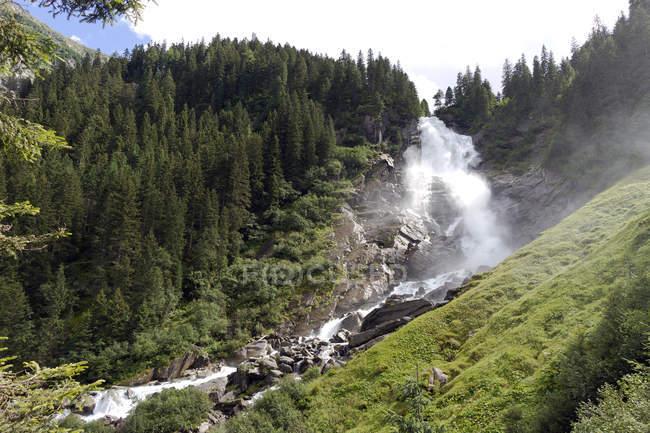 Austria, Alps, Krimml waterfalls by fir mountain forest — Stock Photo