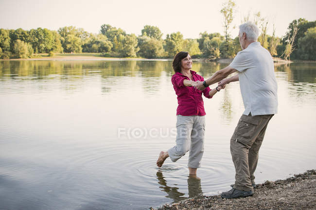 Happy senior couple holding hands at a lake — Stock Photo