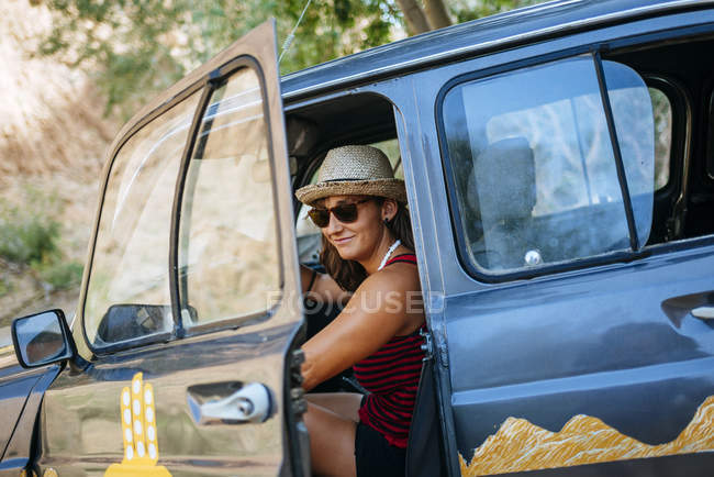 Portrait of smiling woman getting on her car — Stock Photo