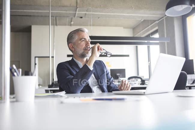 Nachdenklich Geschäftsmann mit Laptop und Gläser im Büro sitzen — Stockfoto