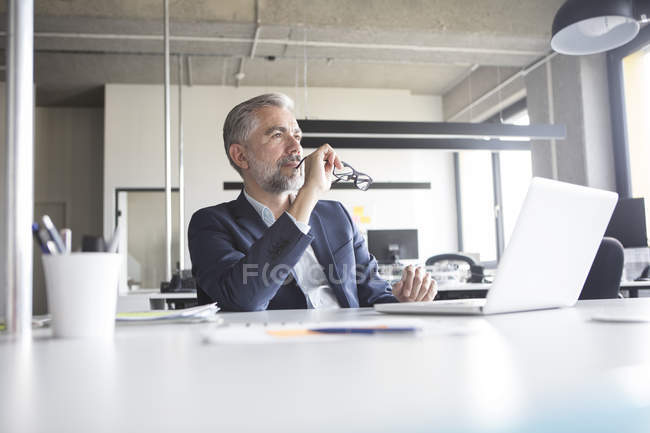 Thoughtful businessman with laptop and glasses sitting in office — Stock Photo