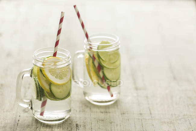 Glasses of infused water with lime, lemon, cucumber and ice cubes — Stock Photo