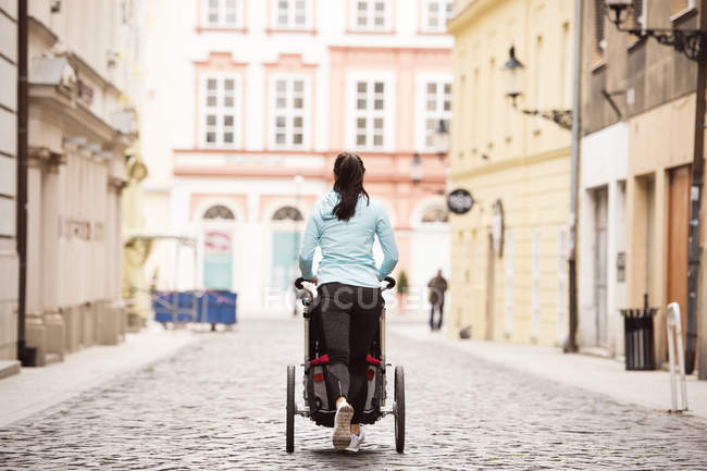 Woman running with stroller in the city — Stock Photo