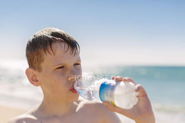 Boy drinking water on the beach — Stock Photo