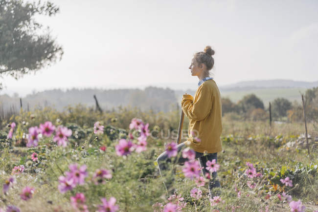 Young woman with spade in cottage garden — Stock Photo