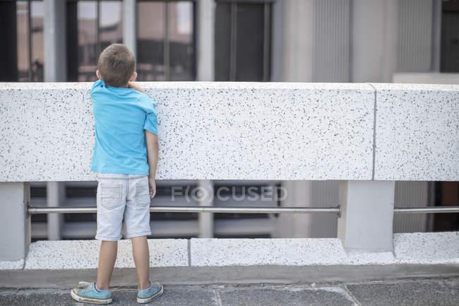 Vue arrière de Boy debout sur le pont et regardant au-dessus de la rampe — Photo de stock