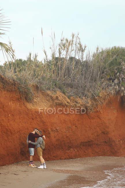 Гей пара обниматься и целоваться на пляже — стоковое фото