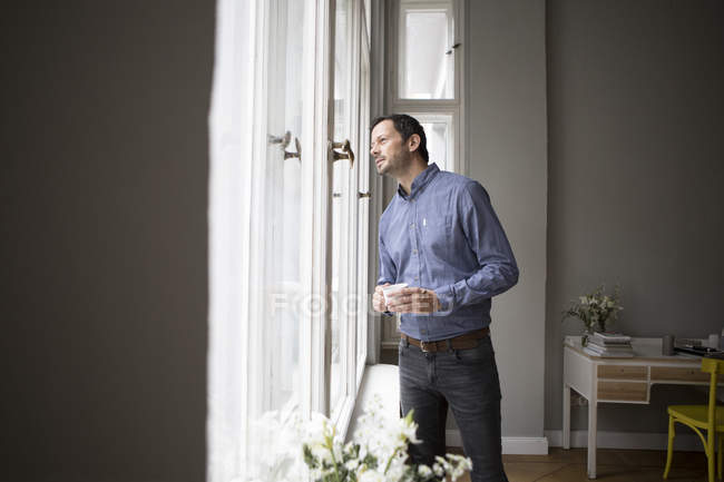 Handsome caucasian man standing by window with coffee cup — Stock Photo