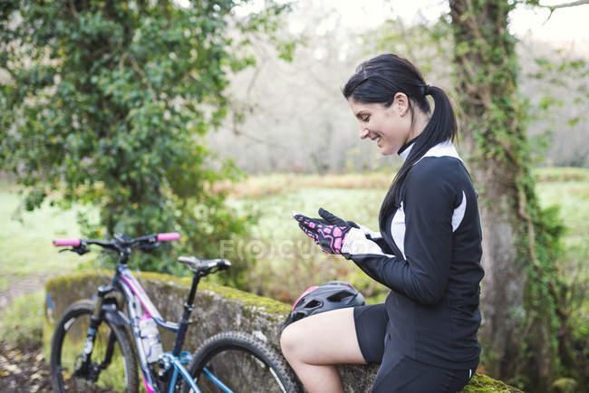 Woman sitting with mountain bike — Stock Photo