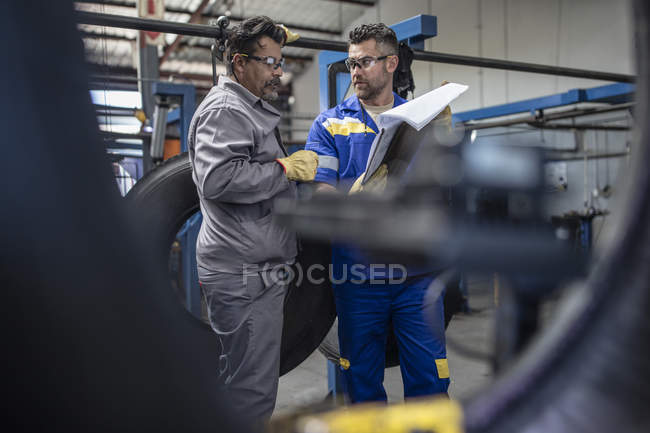 Two tire repairmen with clipboard talking in factory — Stock Photo