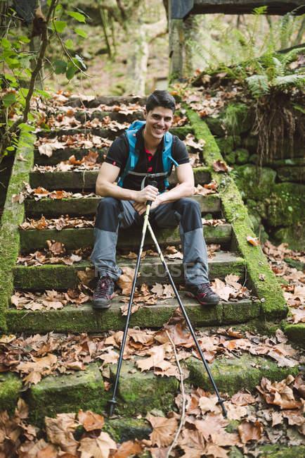 Турист, сидящий на лестнице на природе с тросточками и смотрящий в камеру — стоковое фото