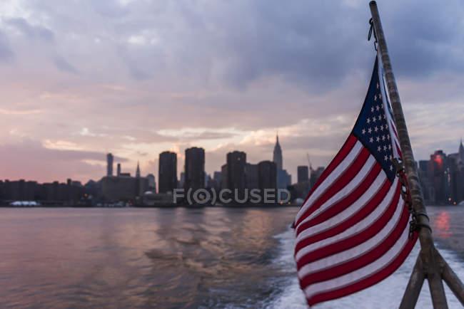 États-Unis, New York, horizon de la ville au coucher du soleil et drapeau américain au premier plan — Photo de stock