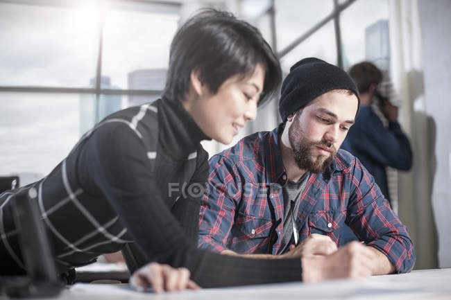 Two casual workers collaborating on project in busy office meeting — Stock Photo