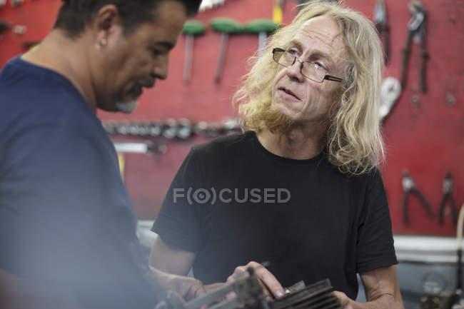 Zwei konzentrierte Mechaniker diskutieren in Werkstatt — Stockfoto