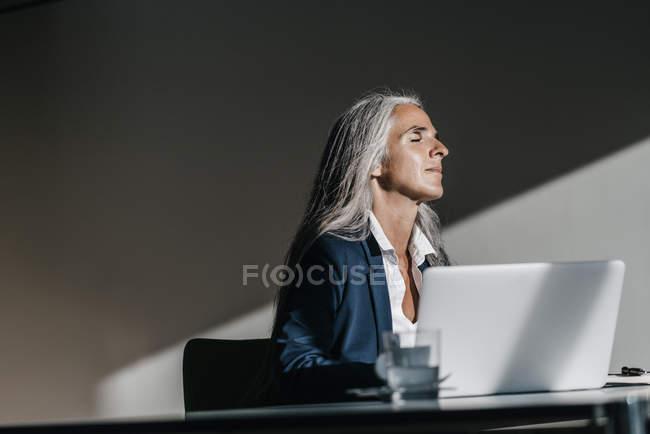 Businesswoman enjoying sunlight at desk in office — Stock Photo