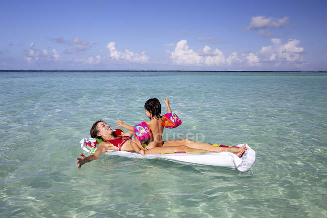 Maldives, Gulhi, mother and daughter playing with inflatable airbed in shallow water — Stock Photo