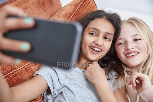 Two laughing girls looking at smartphone together — Stock Photo
