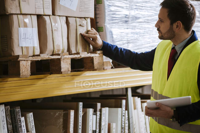 Man in warehouse supervising stock — Stock Photo