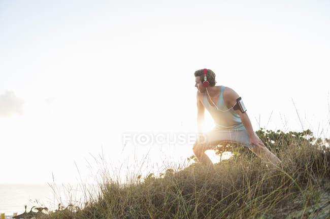 Бігун розтягування на пляжі в ранок у підсвічуванням — стокове фото