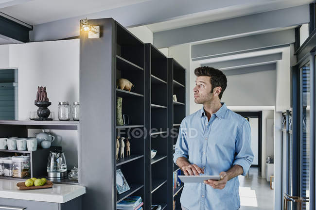 Man regulating lamp with digital tablet — Stock Photo