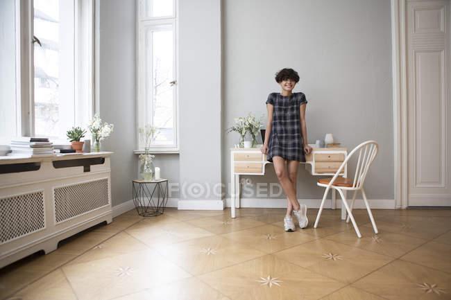 Feliz joven mujer de pie en casa y mirando a la cámara - foto de stock