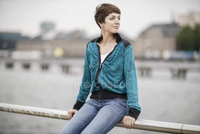 Giovane donna seduta su ringhiera e guardando la vista — Foto stock
